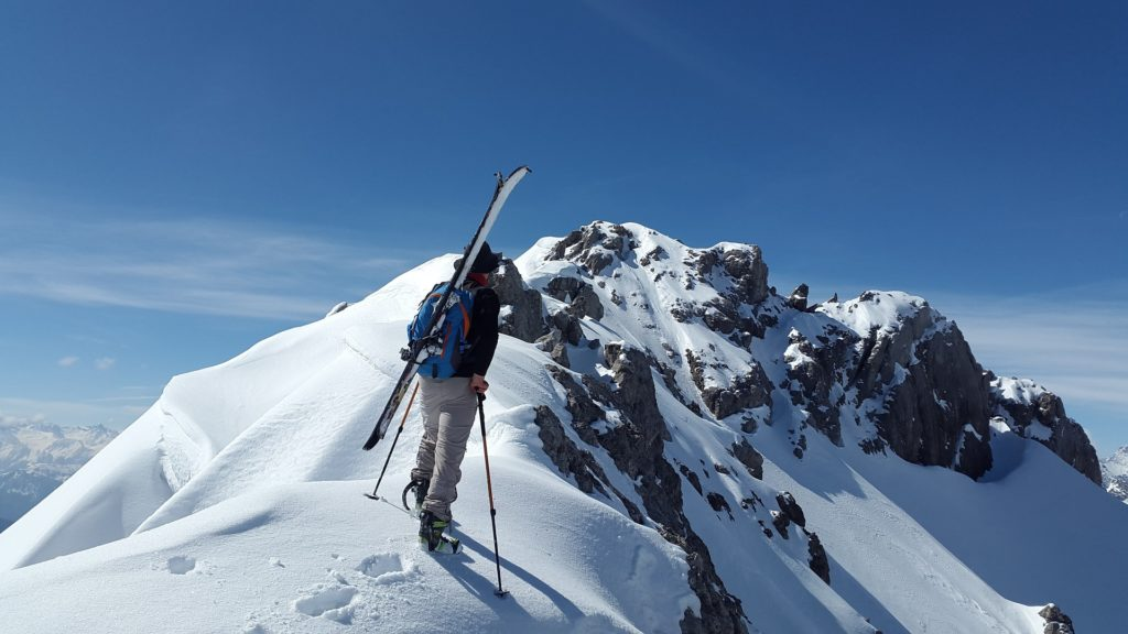 Wejście na szczyt z nartami przyczepionymi do plecaka
